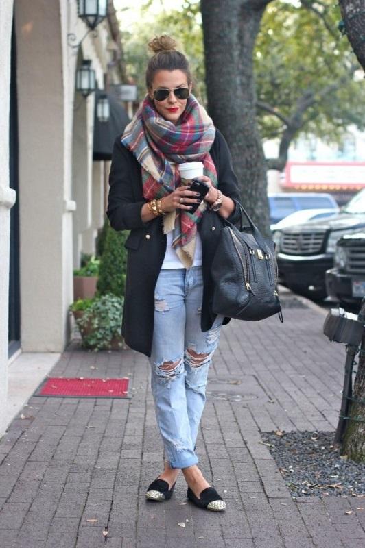 Девушка в балетках, голубых рваных джинсах, черном пальто и с шарфом хомутом на шее
