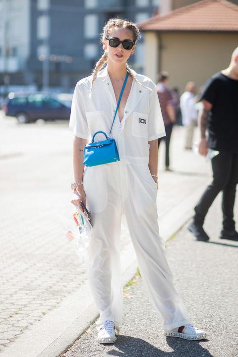 Девушка в белом легком комбинезоне, кроссовках и очках
