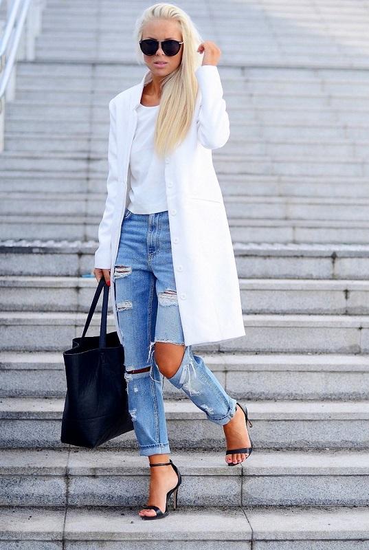 Девушка в белом пальто, рваных джинсах и черных босоножках