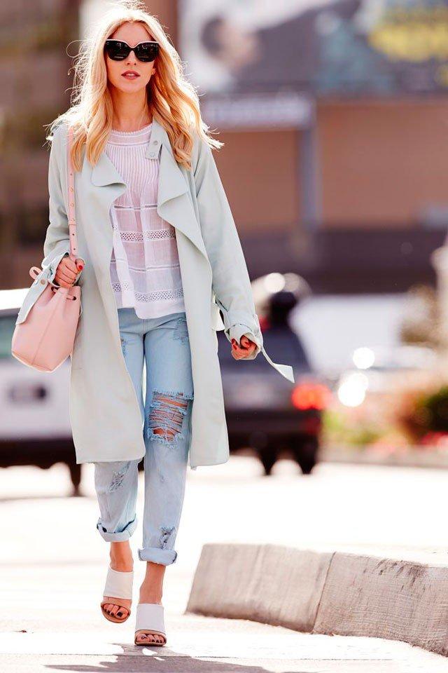 Девушка в белых сандалиях, голубых рваных джинсах и пальто