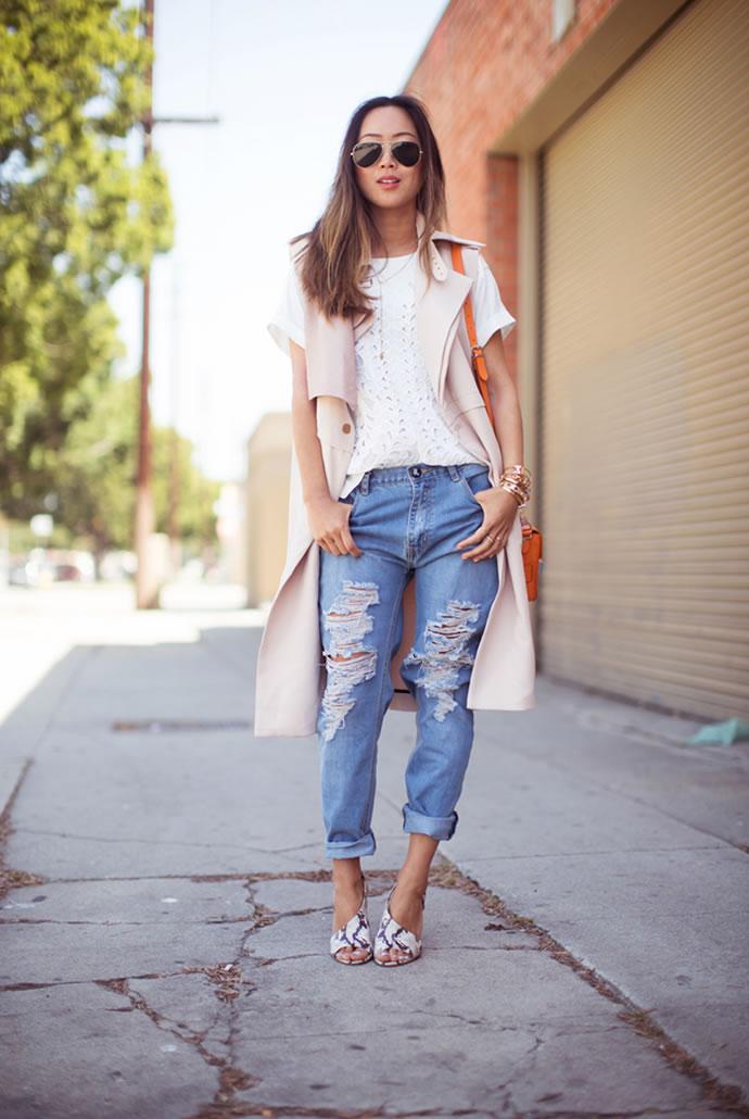 Девушка в бежевых босоножках, рваных джинсах и удлиненном жакете