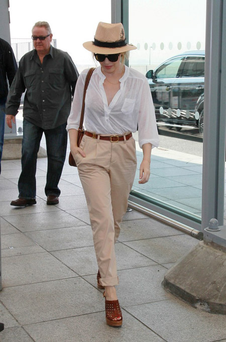 Девушка в бежевых брюках и бежевой шляпе