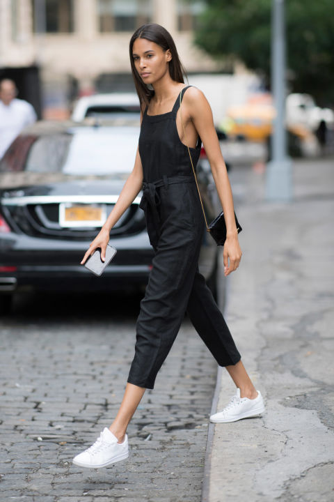 Девушка в черном укороченном комбинезоне и белых кроссовках