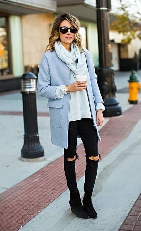 Девушка в черных ботильонах, рваных на коленках джинсах и пальто