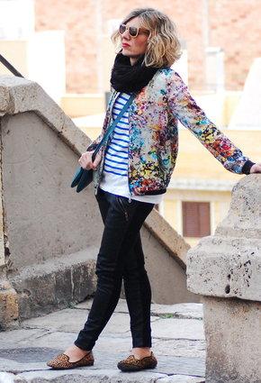Девушка в черных джинсах и цветочном бомбере