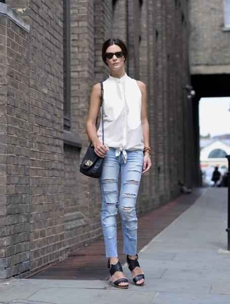 Девушка в черных сандалиях, рваных джинсах и белой блузе без рукавов