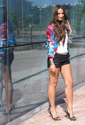 Девушка в черных шортах и цветном бомбере