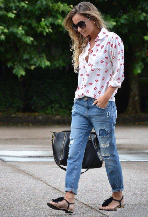 Девушка в рваных синих джинсах, сандалиях и блузе с принтом