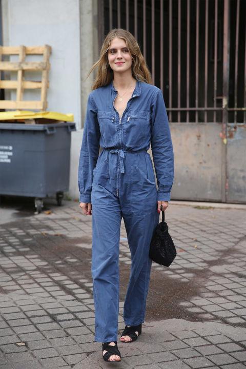 Девушка в джинсовом комбинезоне, босоножках и мешком сумкой