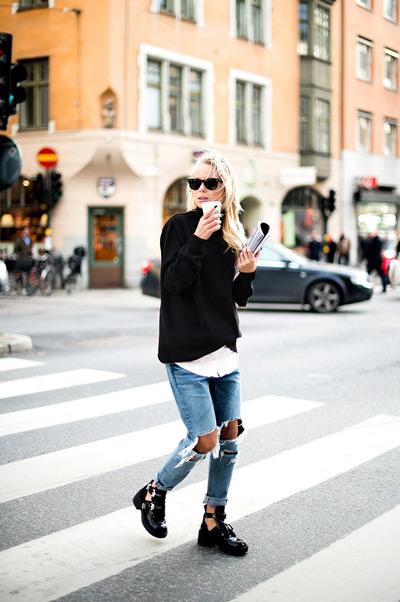 Девушка в грубых ботинках, джинсах с рваными коленками и черном джемпере