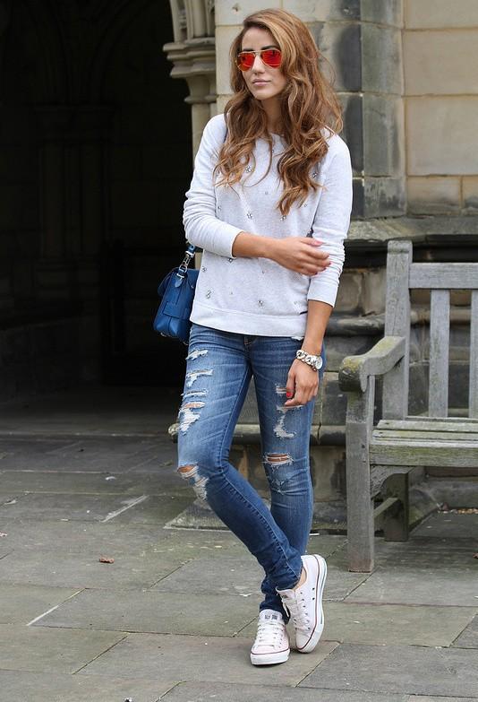 Девушка в конверсах, рваных джинсах и белом джемпере