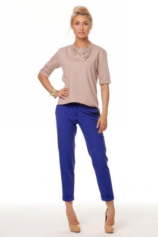 Девушка в пастельной блузке и синих брюках
