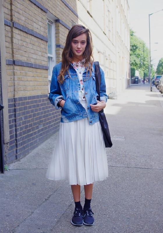 Девушка в плиссированной юбке и джинсовой куртке