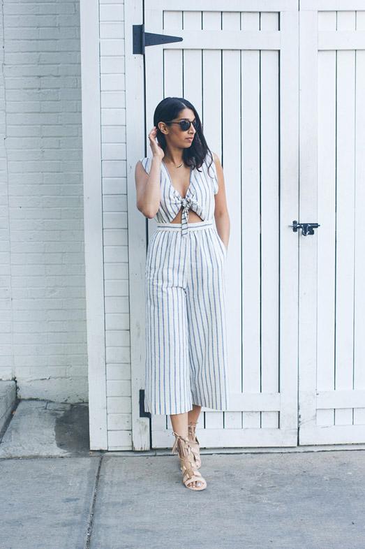 Девушка в полосатом комбинезоне, солнечных очках и сандалиях