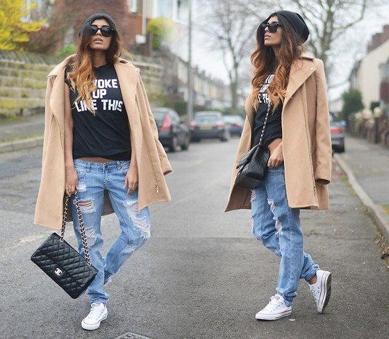 Девушка в рваных бойфрендах, белых кедах, черной футболке и пальто