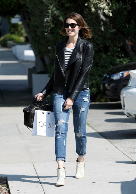 Девушка в рваных джинсах, белых ботильонах и черной кожаной куртке