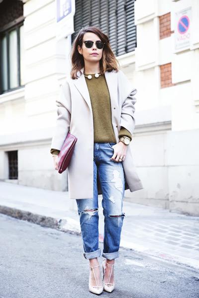 Девушка в рваных джинсах, джемпере и светлом пальто