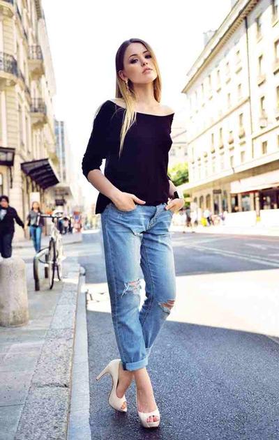 Девушка в рваных джинсах и черном джемпере