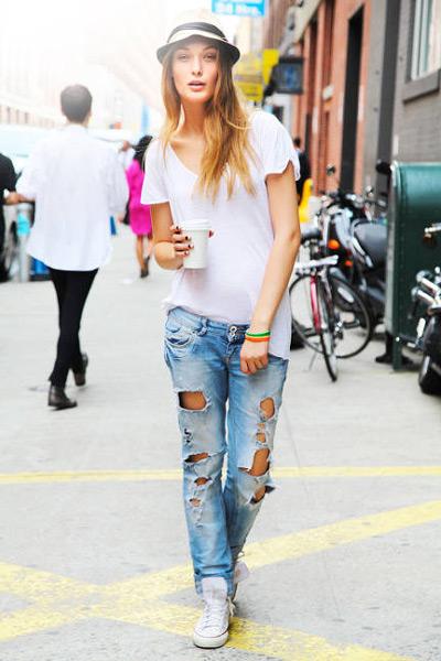 Девушка в рваных джинсах, кедах и белой футболке