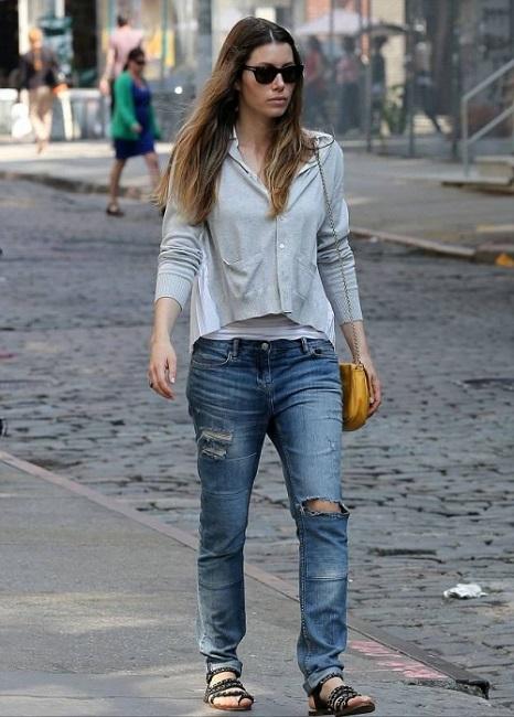 Девушка в рваных джинсах и сандалиях с ремешками
