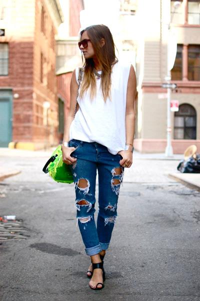 Девушка в рваных джинсах, черных сандалиях и белом топе