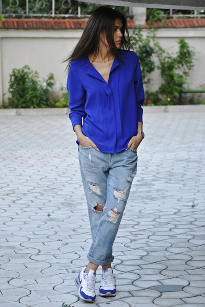 Девушка в рваных джинсах, синей рубашке и кроссовках
