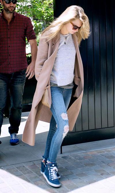 Девушка в рваных джинсах, синих кроссовках и пальто