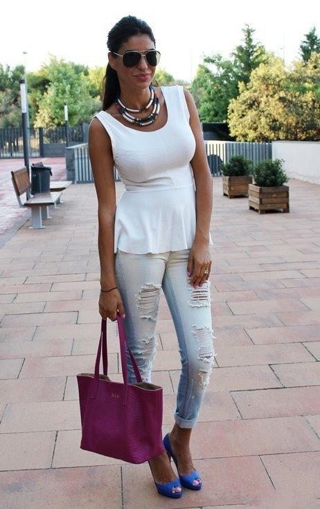 Девушка в рваных джинсах, топе с баской и синих босоножках
