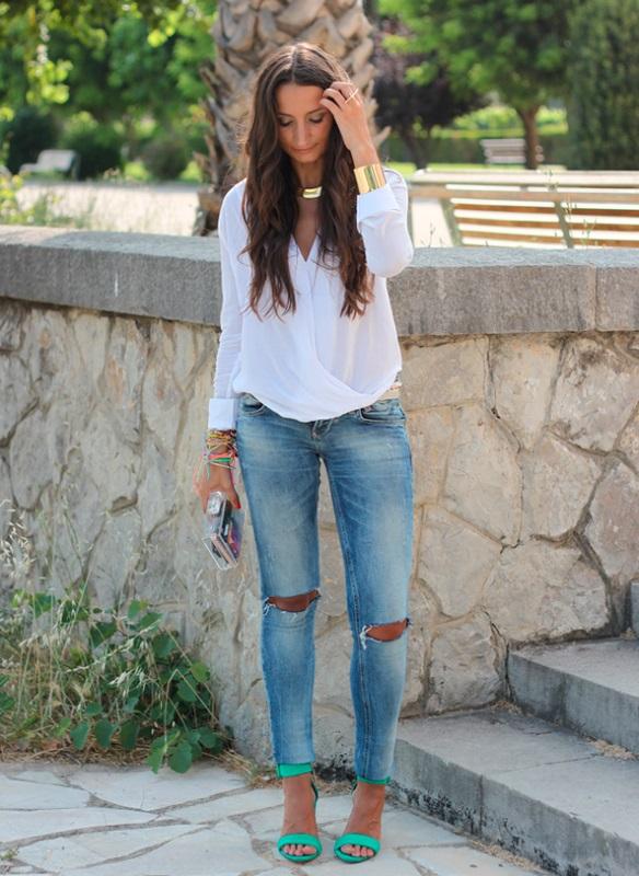 Девушка в рваных джинсах, зеленых босоножках и белой блузе