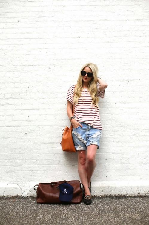 Девушка в рваных джинсовых бермудах и футболка в полоску
