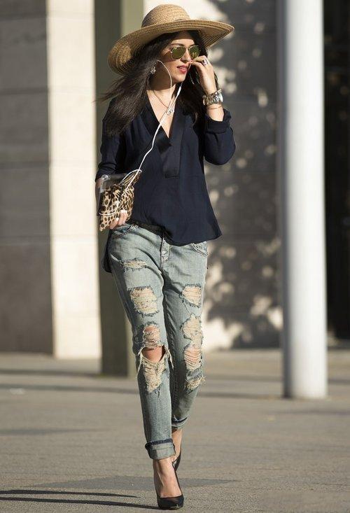 Девушка в серых рваных джинсах, черной блузе и шляпе