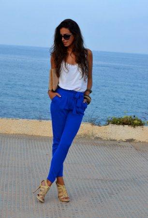 Девушка в синих брюках и белом топе