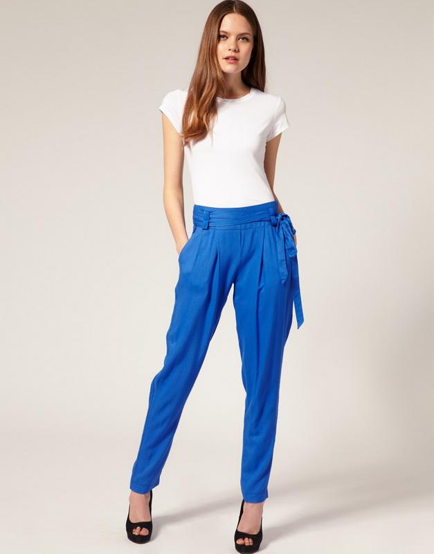 Девушка в синих брюках и белой футболке