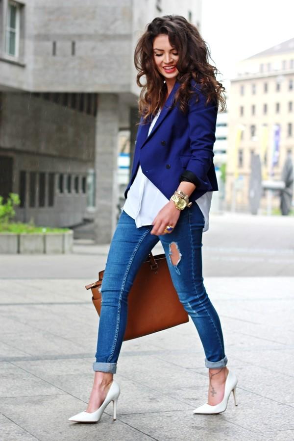 Девушка в слегка рваных джинсах, белых лодочках и синем жакете