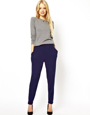 Девушка в темно-синих брюках и сером джемпере