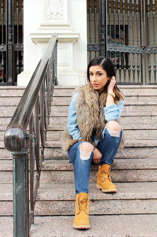 Девушка в тимбелэндах, джинсах с рваными коленками и меховом жилете