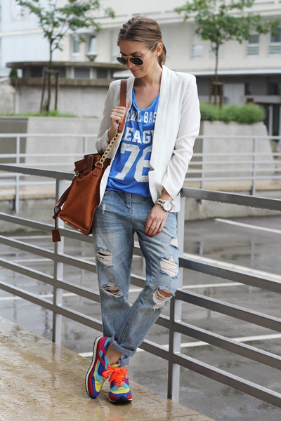 Девушка в ярких кроссовках, рваных бойфрендах и светлом жакете