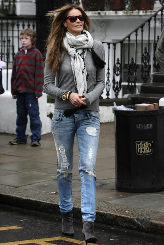 Девушка в замшевых ботильонах, рваных джинсах и сером джемпере