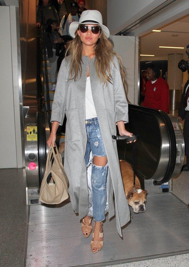 Кристи Тиген в рваных джинсах, длинном сером пальто и шляпе
