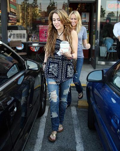Майли Сайрус в рваных джинсах и топе с принтом