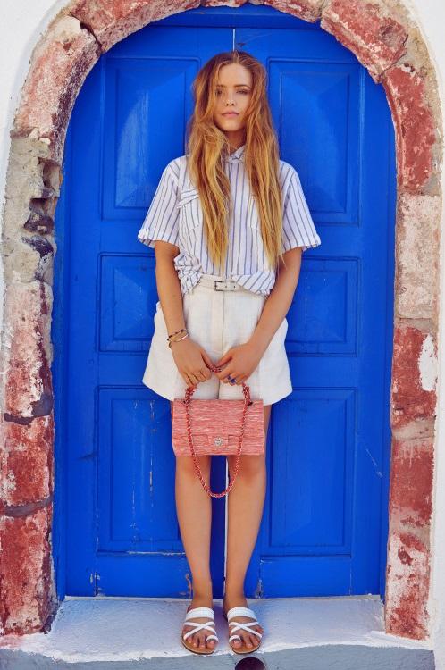 Модель в укороченных шортах-бермудах и белой рубашке в полоску