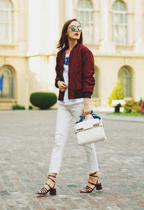 Девушка в белых джинсах, босоножках и бордовом бомбере