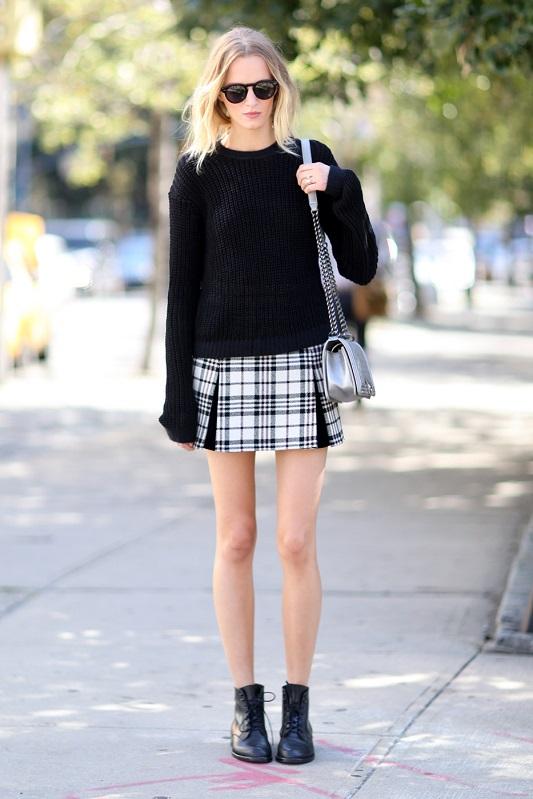 Девушка в черном свиншоте и мини юбке в черно-белую клетку