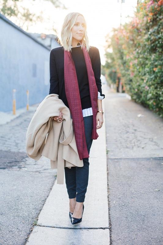 Девушка в джемпере, джинсах и тонком шарфе на шее