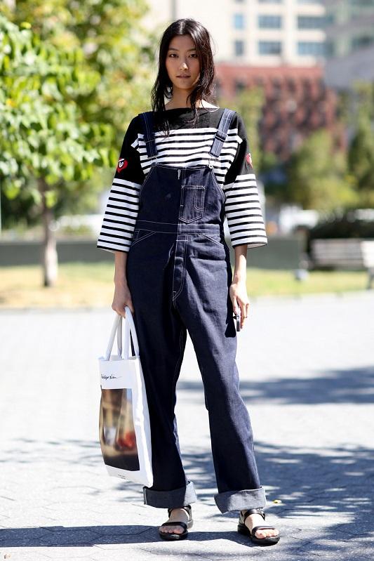 Девушка в джинсовом комбинезоне на лямках и кофте в горизонтальную полоску
