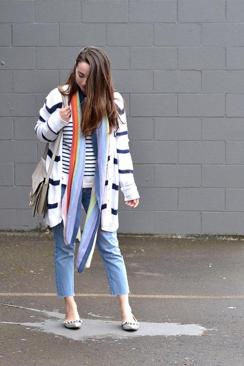 Девушка в обрезанных джинсах, полосатом кардигане и с шарфом на шее