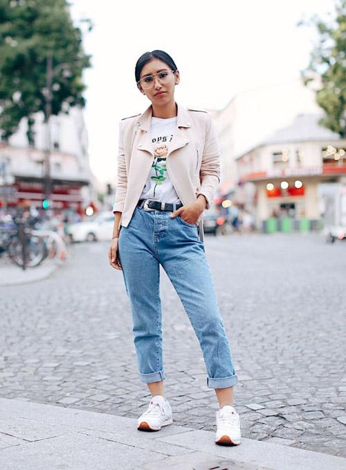Девушка в подвернутых джинсах, кросовках и куртке