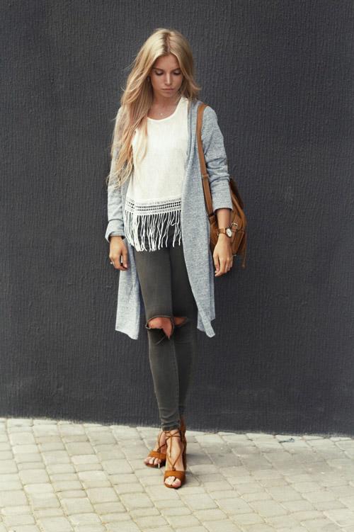 Девушка в рваных джинсах, белой футболке и кардигане