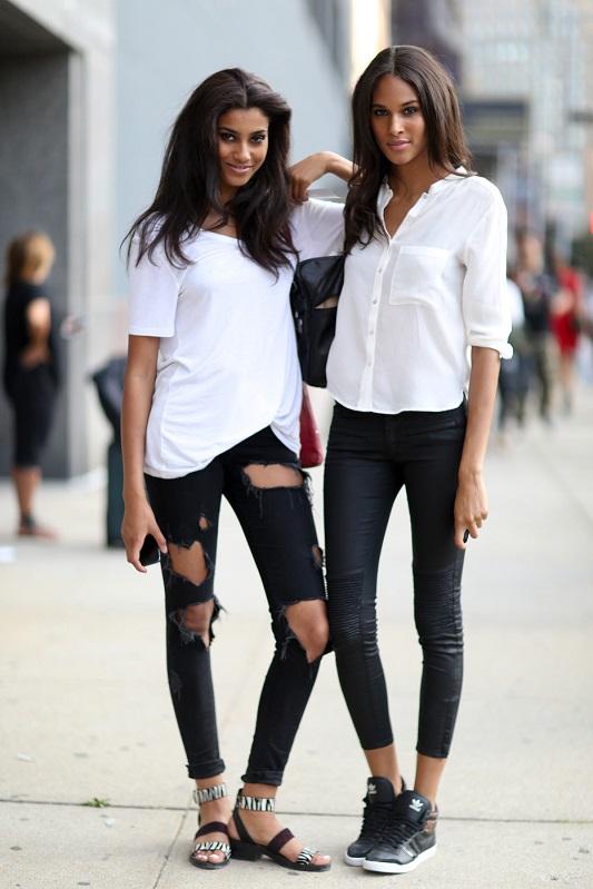 Девушка в рваных джинсах и белой футболке и девушка в черный легинсах и белой блузе