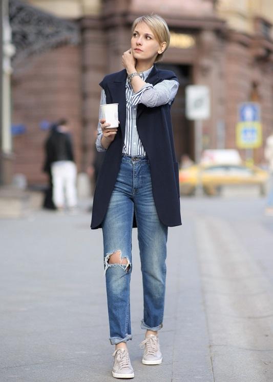 Девушка в рваных джинсах и жилете